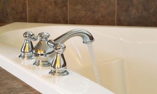 Closeup horizontal photo of chrome faucet running water into soaking tub in master bathroom